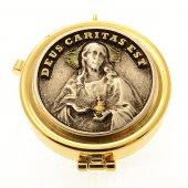 "Teca eucaristica porta ostie con placca bronzata in rilievo ""Deus caritas est"" - diametro 5,3 cm"